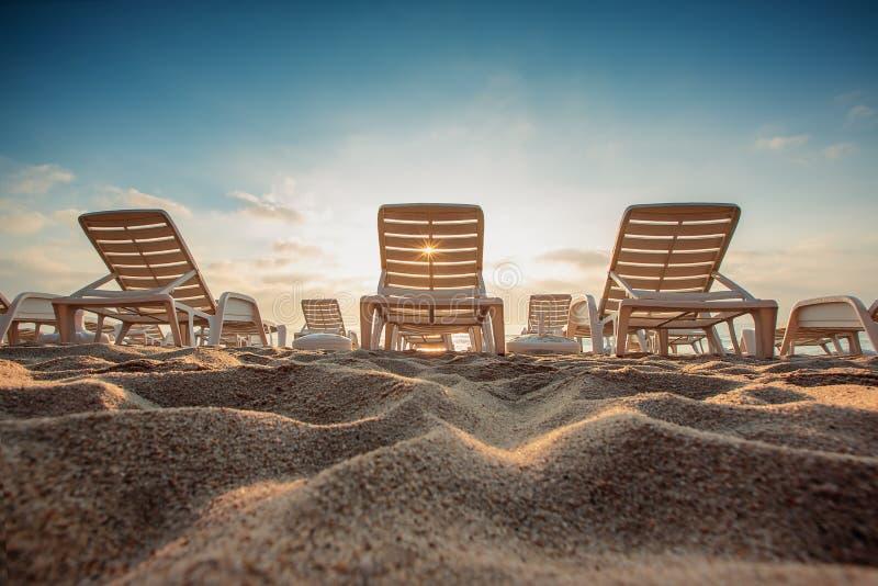 在异乎寻常的热带海滩,日出射击的海滩睡椅 库存照片