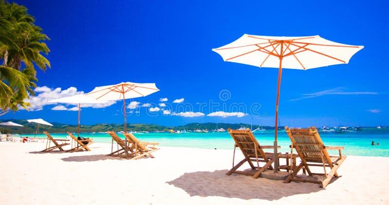 在异乎寻常的热带白色沙滩的海滩睡椅 免版税库存照片