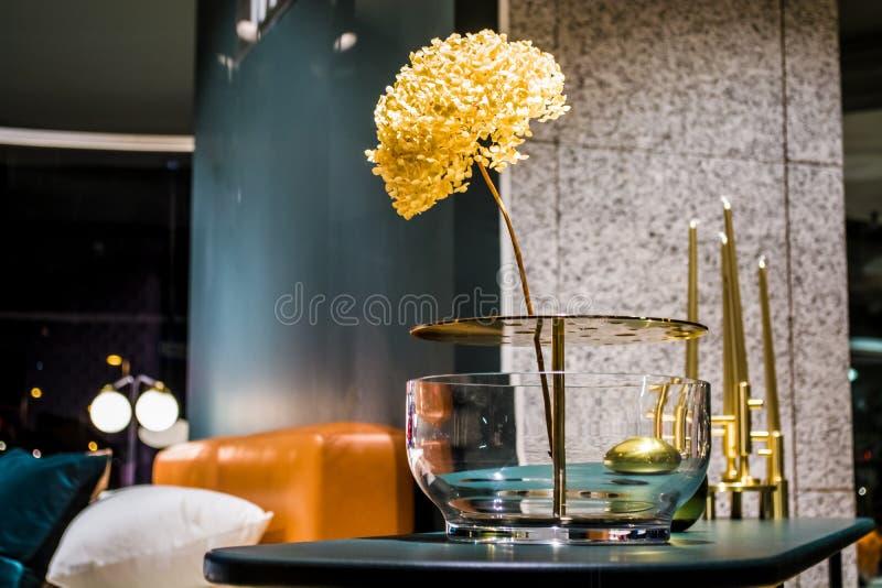 在异常的玻璃花瓶的美丽的花在公寓内部  房子和办公室的装饰 工厂 因为极大创建的基础使材料自然这样对木工作运作 免版税库存照片