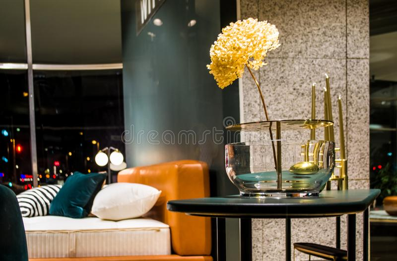在异常的玻璃花瓶的美丽的花在公寓内部  房子和办公室的装饰 工厂 因为极大创建的基础使材料自然这样对木工作运作 免版税图库摄影