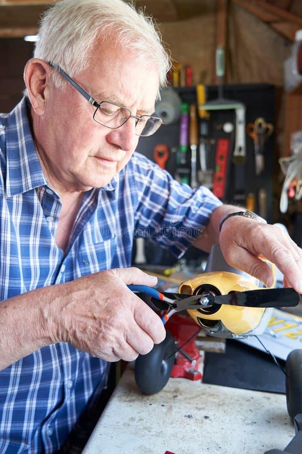 在式样无线电操纵的Aieroplane的老人工作在棚子在家 免版税库存图片
