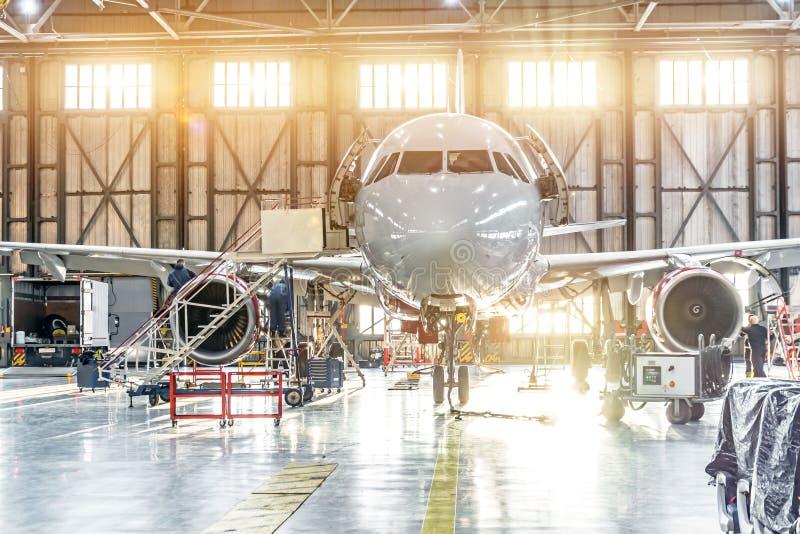 在引擎修理维护的客机在机场飞机棚 免版税库存照片
