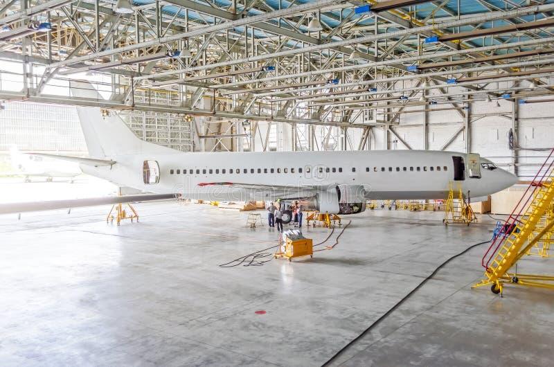 在引擎维护,检查修理的乘客飞机在机场飞机棚 航空器侧视图,开放飞机棚门 图库摄影