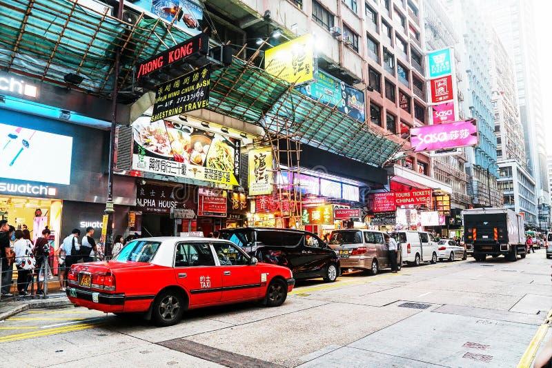 在弥敦道的典型的城市生活,香港 路人和公路交通、大厦和标志 免版税库存图片