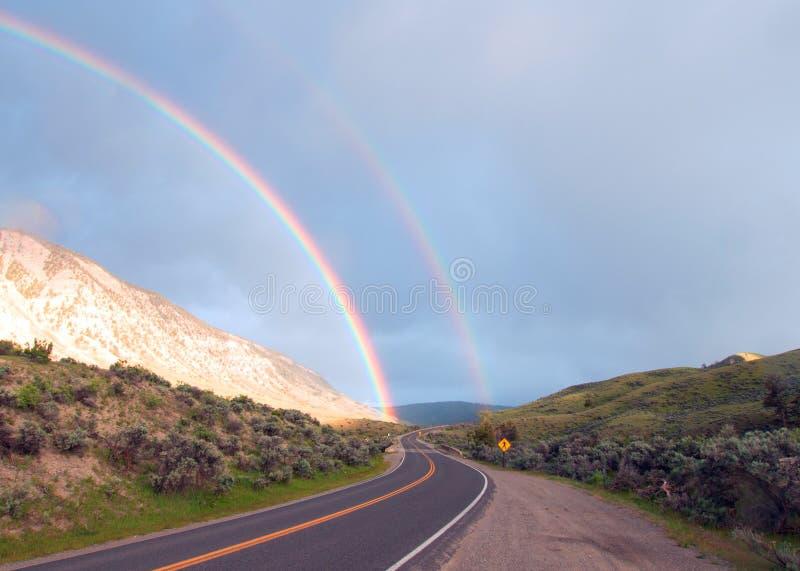 在弯曲的路的双重彩虹向马默斯斯普林斯在黄石国家公园在怀俄明美国 库存照片