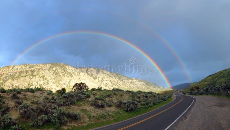 在弯曲道路的双重彩虹向马默斯斯普林斯在黄石国家公园在怀俄明美国 库存照片