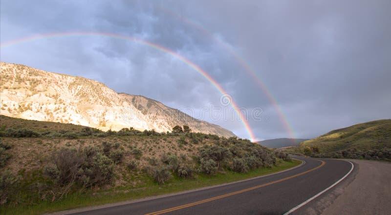 在弯曲道路的双重彩虹向马默斯斯普林斯在黄石国家公园在怀俄明美国 免版税库存照片