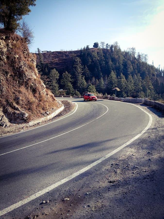 在弯曲道路的红色汽车 免版税库存照片