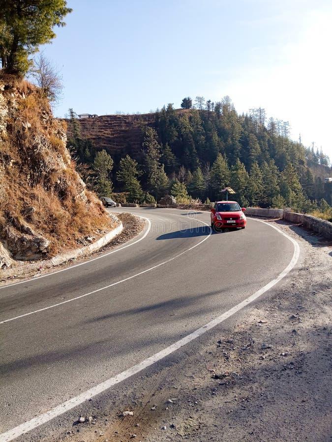 在弯曲道路的红色汽车 免版税库存图片