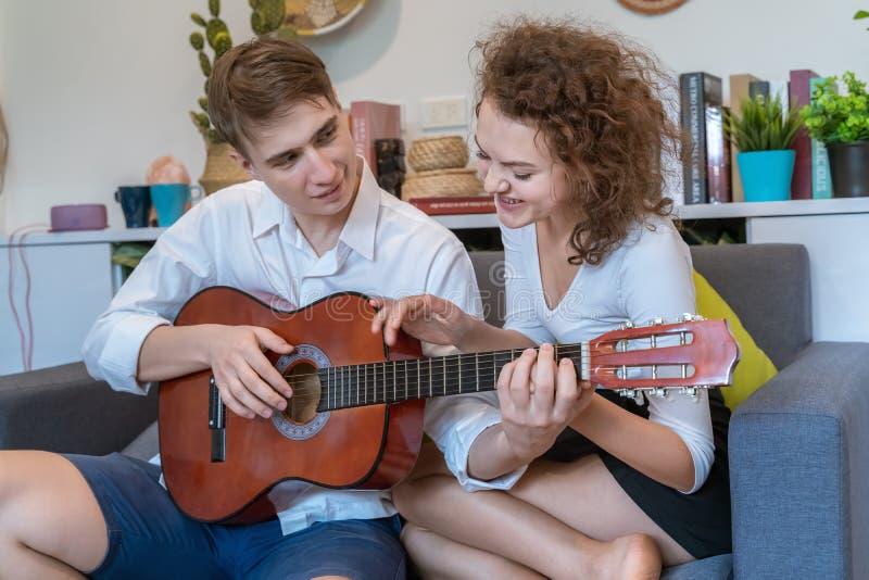 在弹吉他期间,青少年的夫妇互相戏弄 免版税库存照片