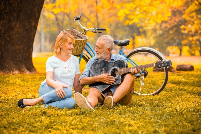 在弹声学吉他的爱的愉快的资深夫妇在公园在与自行车的大树下在秋天 库存照片
