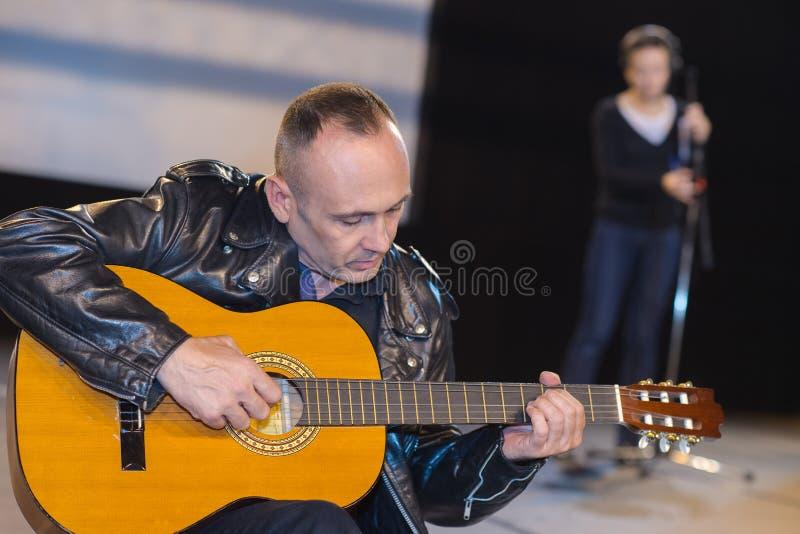 在弹电吉他的录音室供以人员坐 图库摄影