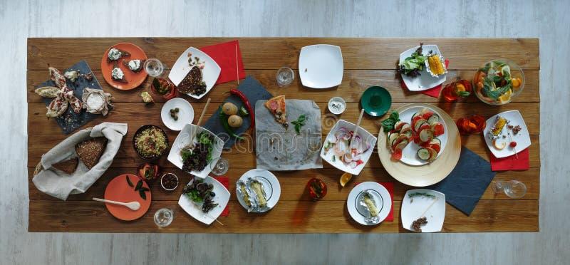 在当事人以后 在木服务的欢乐桌上的被浪费的食物 免版税库存照片