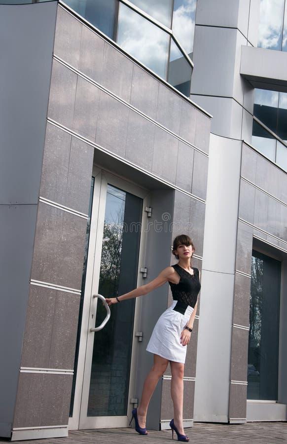 在当代大厦附近的俏丽的女商人 图库摄影