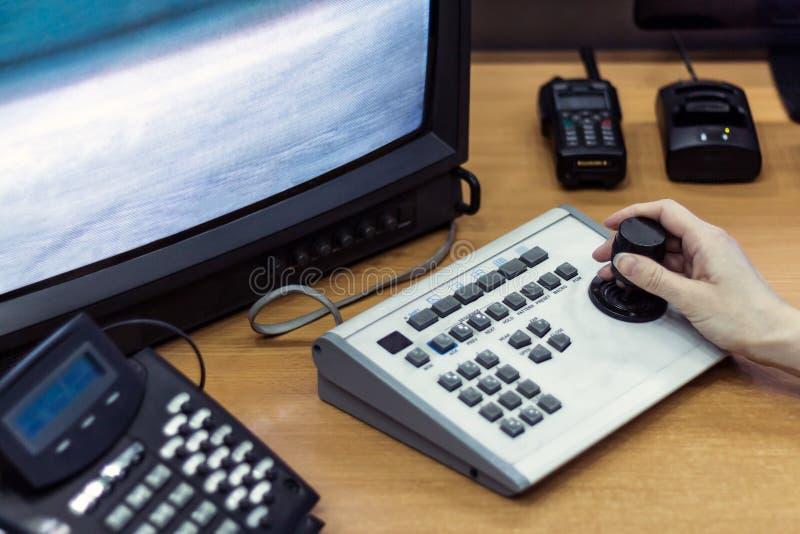 在录影监视控制板的女性手  在显示器旁边的携带无线电话 工作场所 Cctv 库存照片