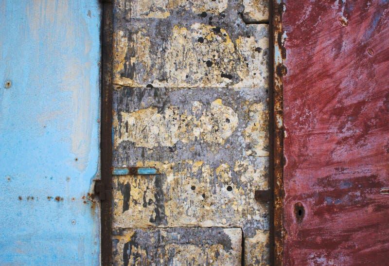 在形成脏的抽象纹理背景的砖和水泥粗砺的墙壁的蓝色和红色被绘的金属门 免版税库存照片