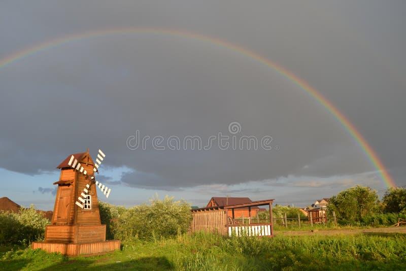 在彩虹下的风车 免版税库存图片