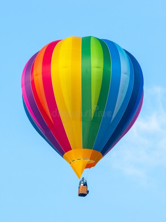 在彩虹光谱颜色的热空气气球在蓝天背景 免版税库存照片