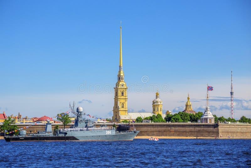 在彼得和保罗堡垒背景的小反潜艇船Urengoy在海军游行前的在俄国舰队的那天 免版税图库摄影
