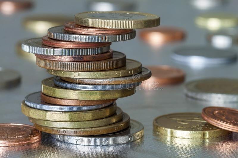在彼此发光的硬币不同的大小和颜色参差不齐地堆积的两堆在五颜六色的被弄脏的蓝色抽象背景 库存图片