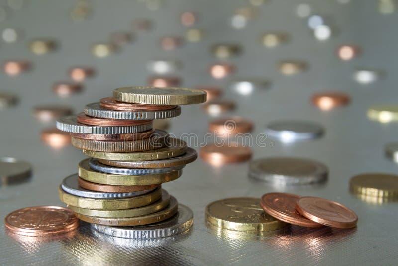 在彼此发光的硬币不同的大小和颜色参差不齐地堆积的堆在五颜六色的被弄脏的蓝色抽象背景 ?? 免版税库存照片