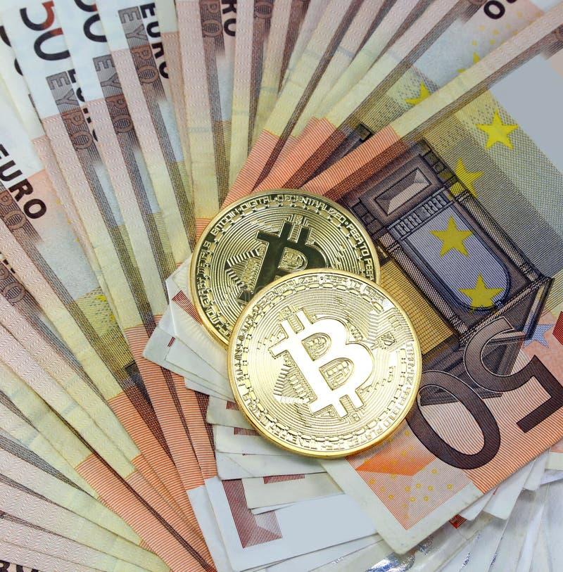 在很多欧洲钞票的两枚金黄BitCoin硬币 图库摄影