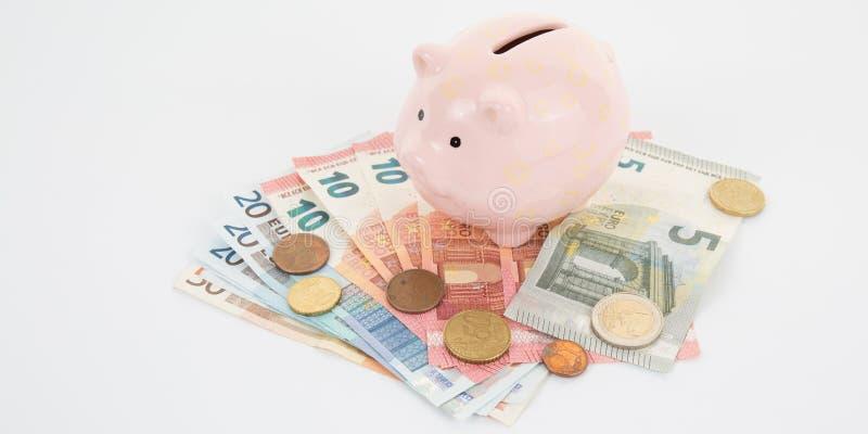 在很多硬币和欧洲票据的桃红色存钱罐 库存图片