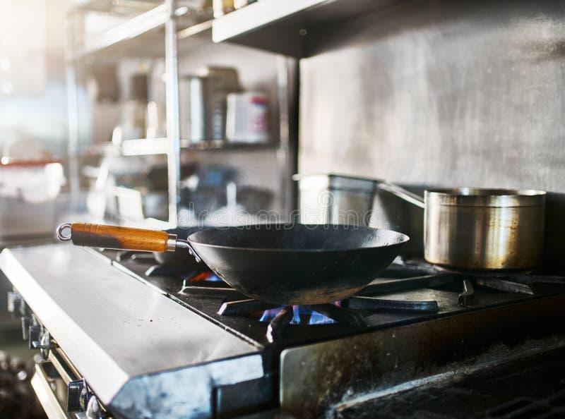 在得到的煤气炉的铁锅热在商业餐馆厨房里 库存照片
