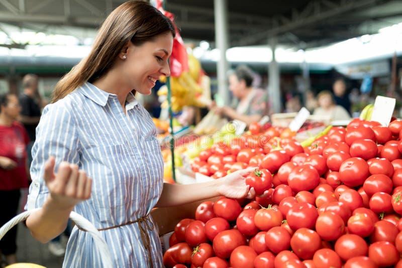 在得到食物的市场上的美丽的年轻深色的妇女 免版税库存图片