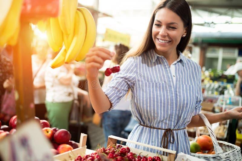 在得到食物的市场上的美丽的年轻深色的妇女 库存图片