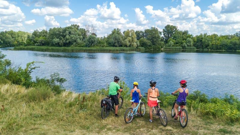 在循环的自行车户外,活跃父母和孩子的家庭在自行车,愉快的家庭鸟瞰图与儿童放松的 库存照片