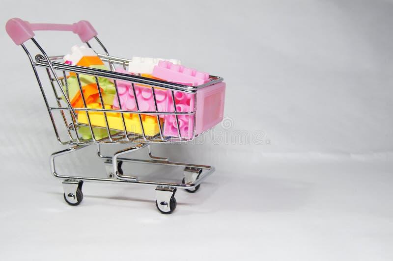 在微型购物的台车里面的乐高块 免版税图库摄影
