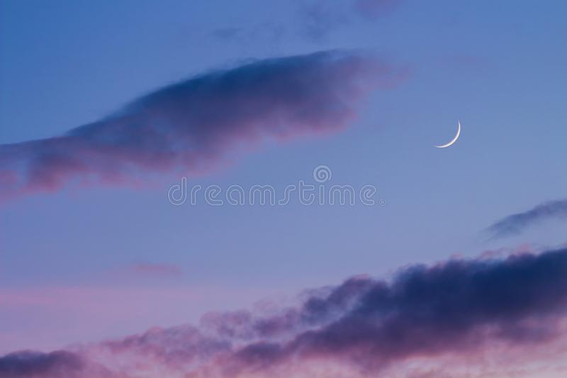 在微明的银色月亮与紫色天空 库存照片