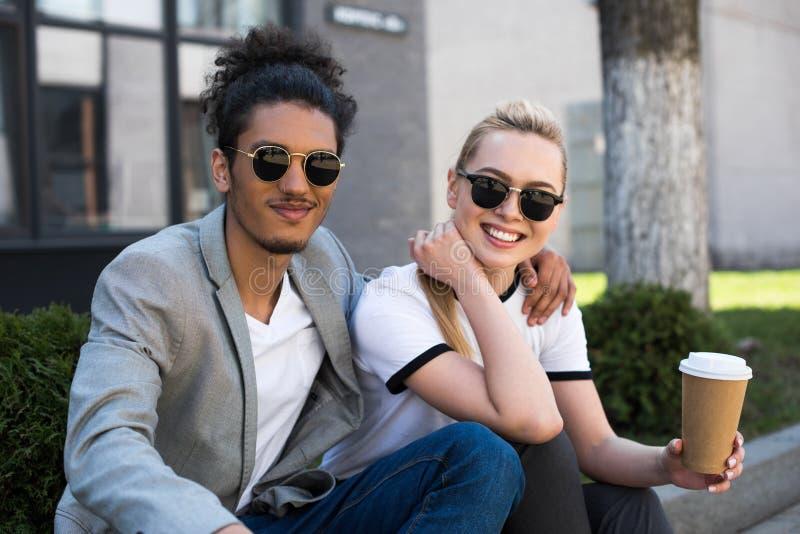 在微笑对照相机的太阳镜的年轻不同种族的夫妇,当喝咖啡去时 免版税库存照片