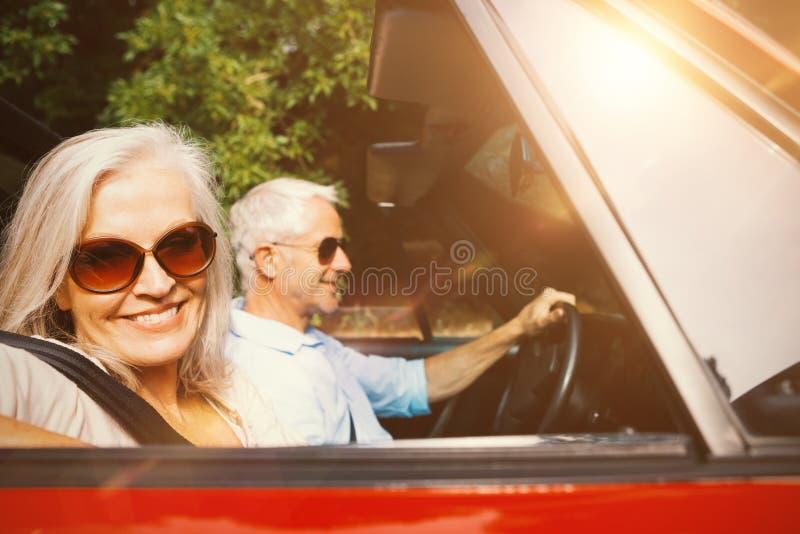 在微笑对照相机的汽车的老夫妇 免版税库存照片