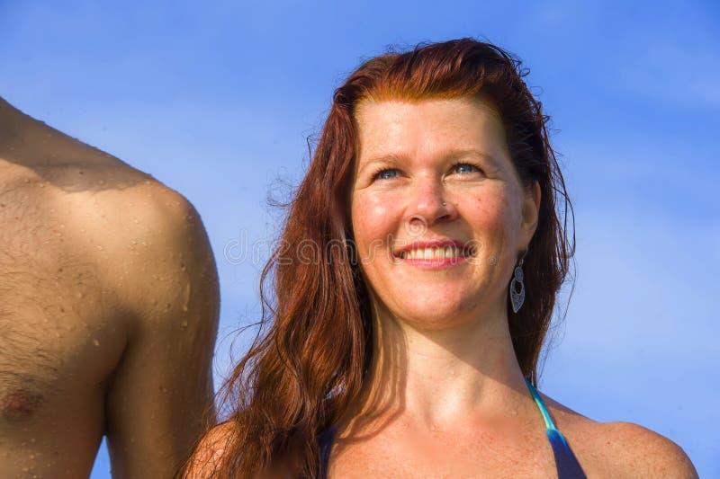 在微笑海滩withl红色头发的妇女的年轻美好和愉快的夫妇比基尼泳装的快乐和轻松的享用的夏天休 库存照片
