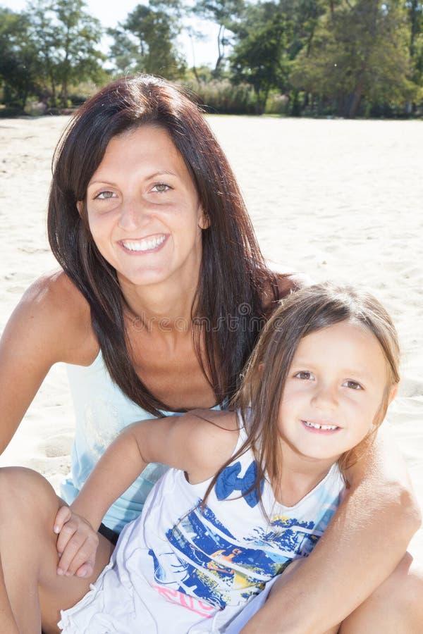 在微笑的母亲白色沙子画象的家庭沙子的乐趣和女儿使晴朗靠岸 免版税库存照片