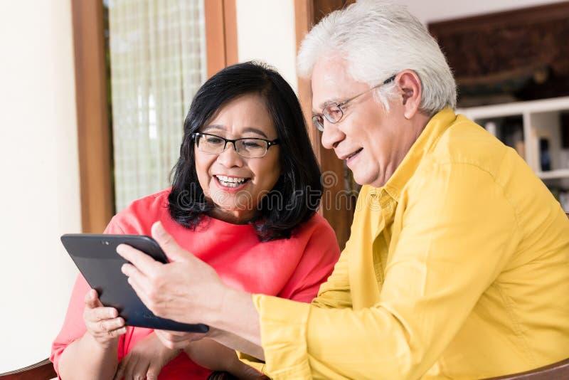 在微笑的爱的亚洲资深夫妇,当拿着片剂时 库存图片
