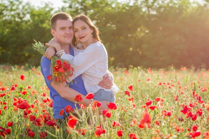 在微笑鸦片的领域中的夫妇拥抱和 免版税库存照片