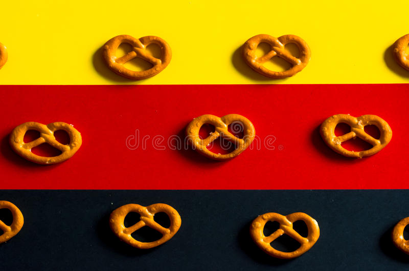 在德国旗子颜色的背景的许多小椒盐脆饼 免版税库存照片