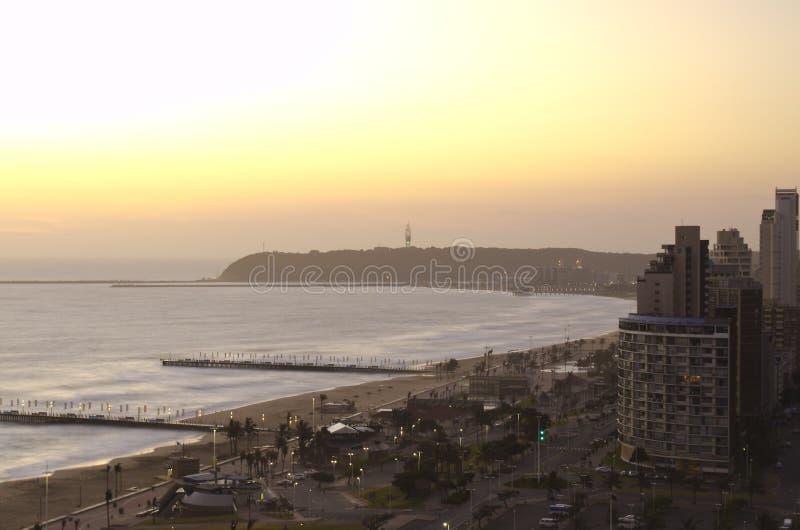 在德班的海滩前面的日出 免版税图库摄影