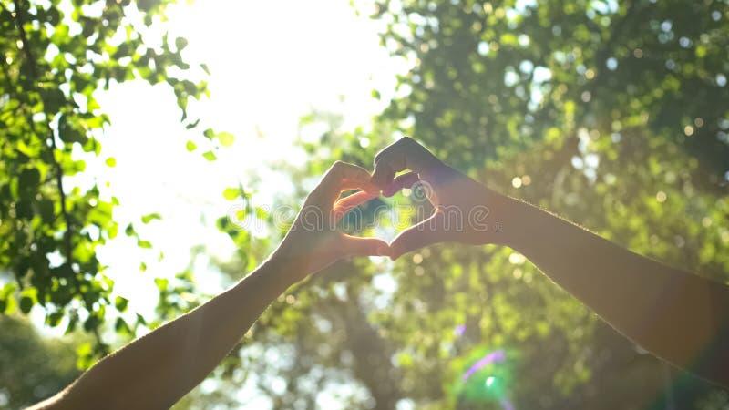 在心形、人种间友谊、爱和关心的多种族夫妇手 免版税库存照片
