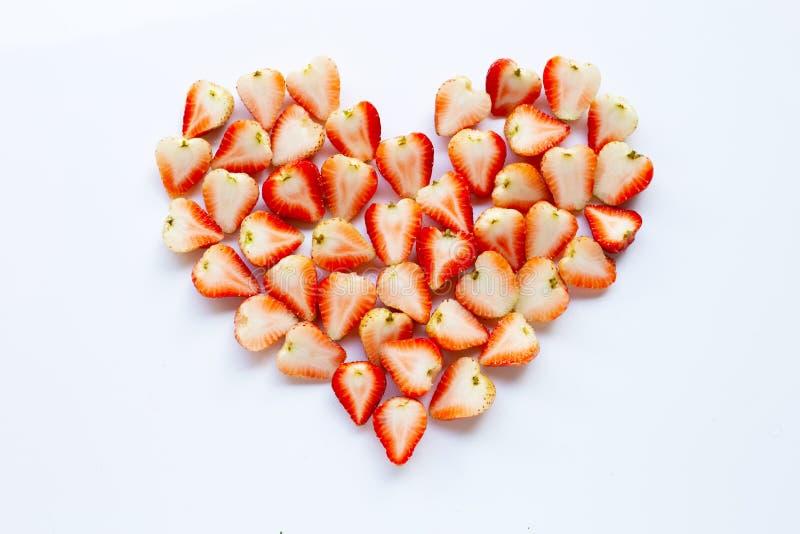 在心形安置的草莓在白色 图库摄影