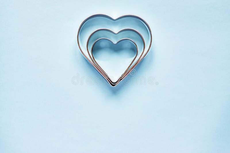 在心形的三把金属曲奇饼切削刀在与拷贝空间的浅兰的背景 免版税库存图片