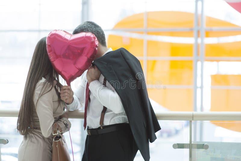 在心形的气球后的男人和妇女亲吻 免版税库存图片