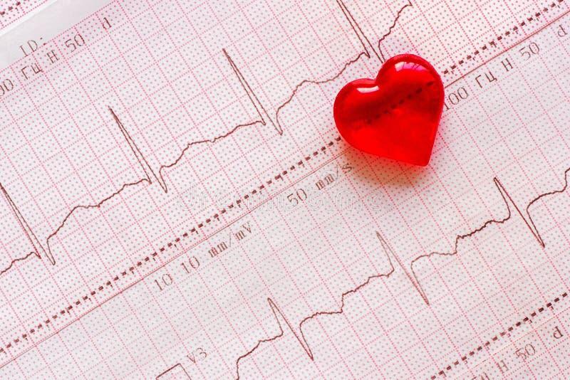 在心电图ECG的背景的塑料心脏 免版税库存图片