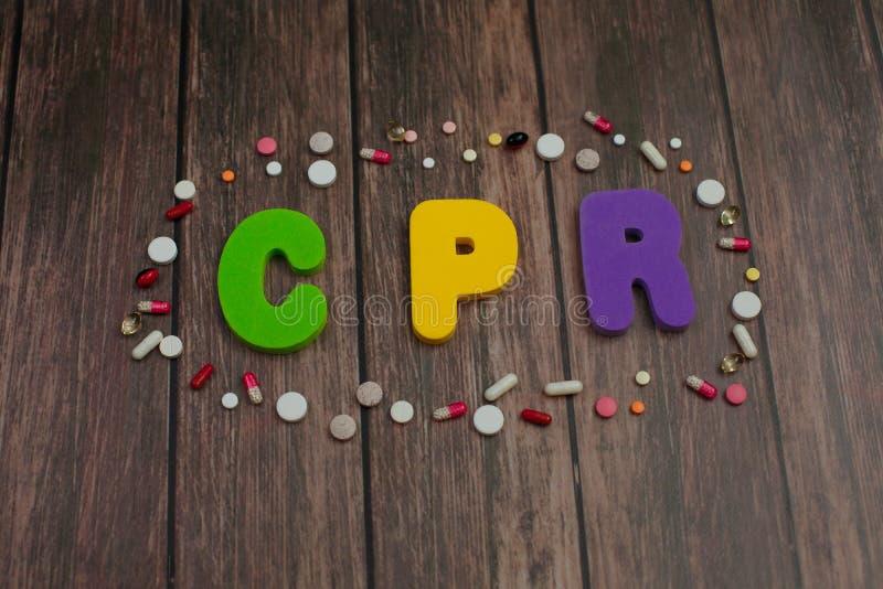 在心肺复苏术的词CPR简称的颜色字母表在药片附近的在木背景 免版税图库摄影