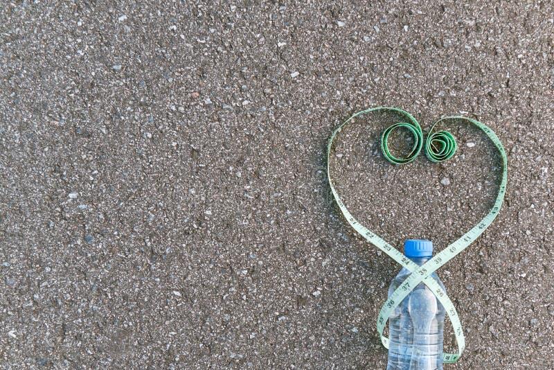 在心脏形式和水瓶的绿色措施磁带 免版税库存照片