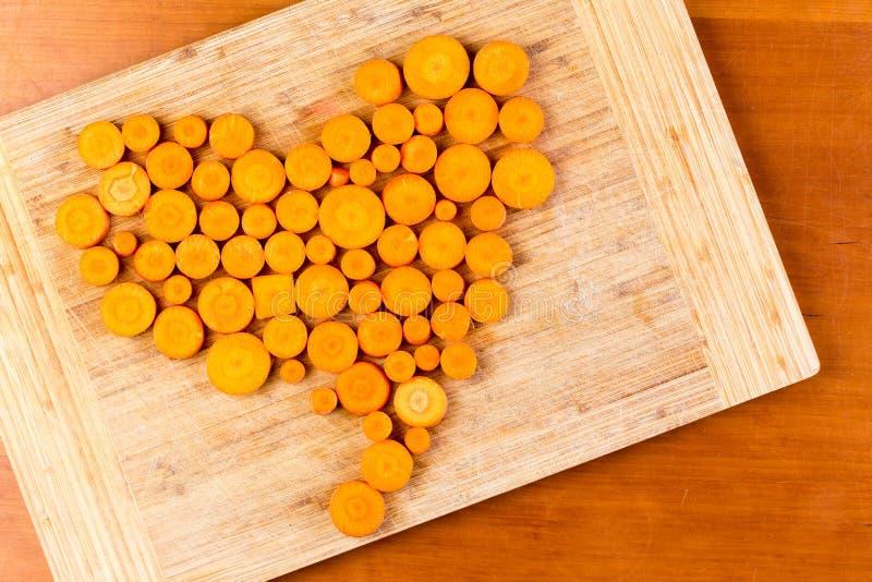 在心脏形状安排的切好的红萝卜 库存图片