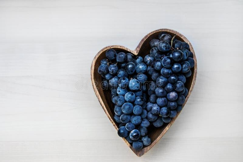 在心脏形状木板材的葡萄 免版税图库摄影